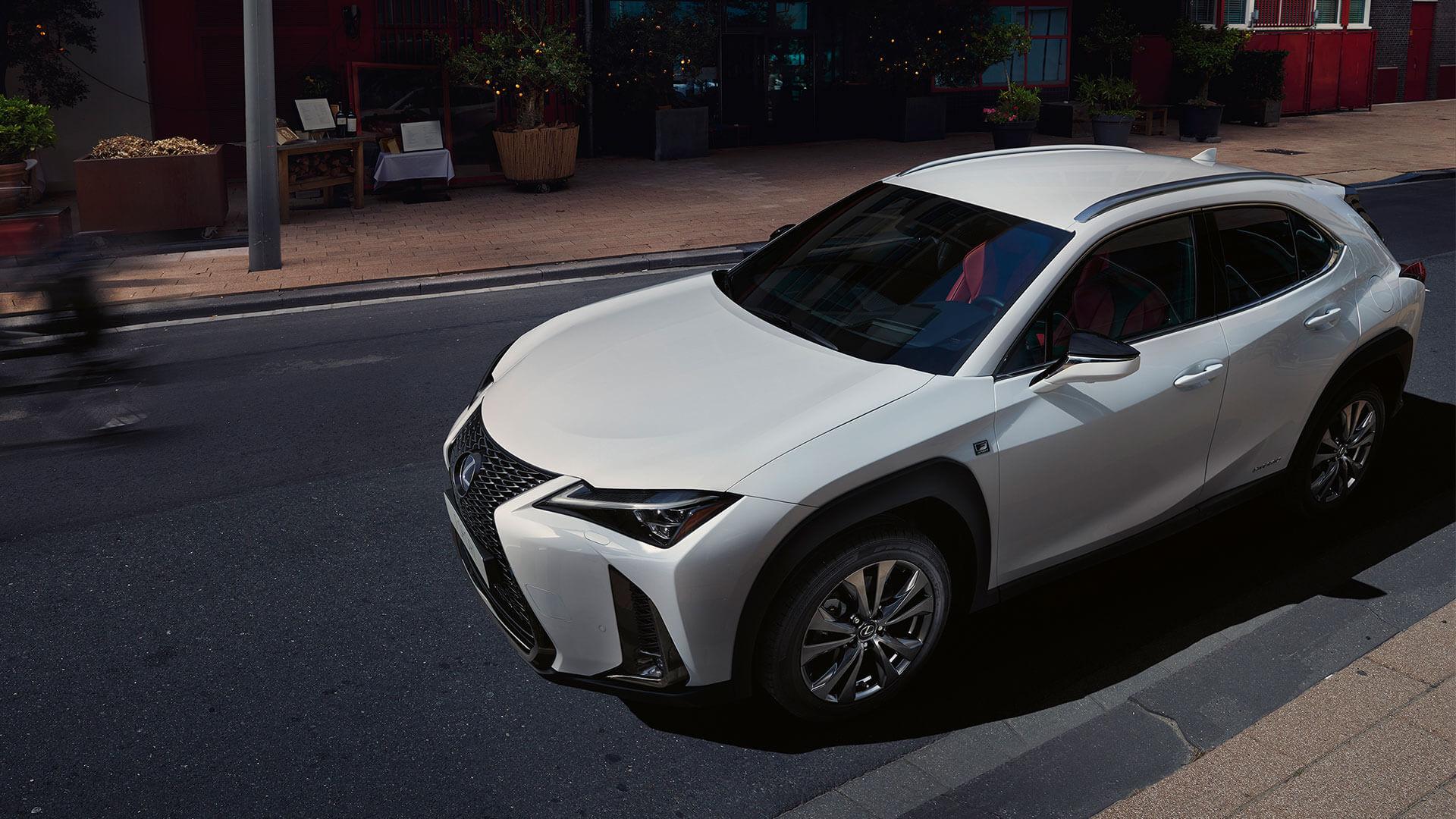 Lexus UX weiß mit Seitenansicht auf Straße