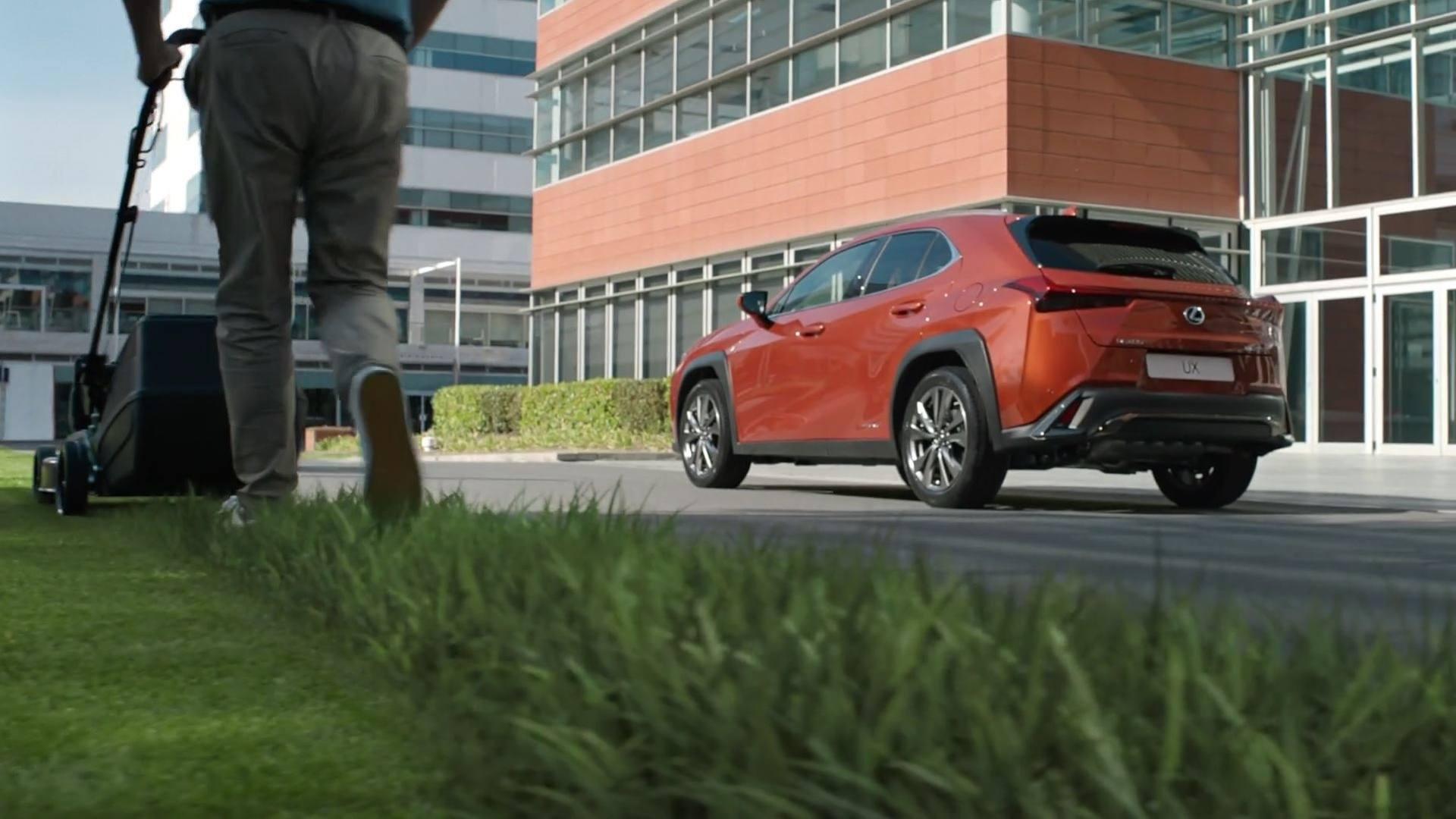 Lexus Hybrid Mann mit Rasenmäher