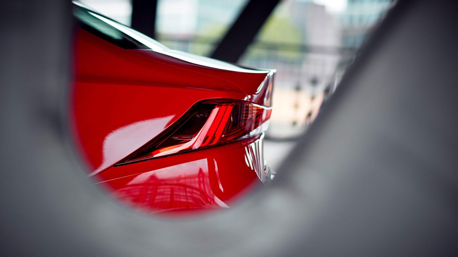 Rød Lexus modell med baklykt i fokus sett igjennom et hull i en vegg